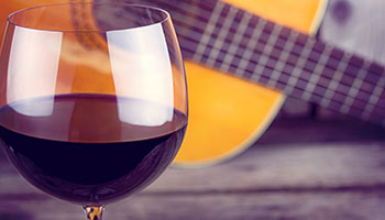 A glass of red wine in front of a brown guitar