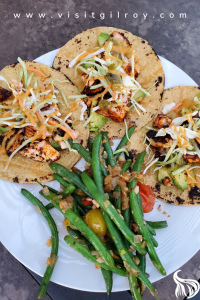 Garlic Blackened Salmon Tacos on a plate with garlic green beans