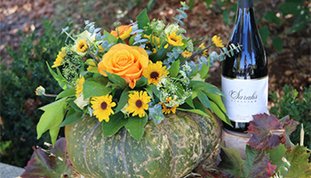 Green pumpkin with orange roses and flowers with a bottle of wine on the side