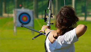 Woman shooting archery on a sunny day