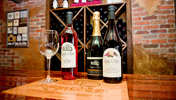 Kirigin Cellars wine on a wooden counter with a single wine glass