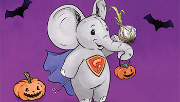 Elephant holding a pumpkin with his trunk with bats flying around him