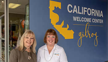 Jane and Pam smiling in front of the California Welcome Center Gilroy